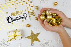 Frohe lerttering Weihnachten Frau hält goldene Weihnachtsbälle und bereitet vor sich, die Feiertage und das Weihnachten zu feiern Lizenzfreie Stockfotografie