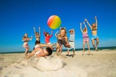 Frohe Leute, die Volleyball spielen Stockfoto