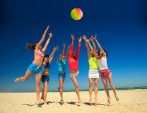 Frohe Mädchen, die Volleyball spielen Stockfotos