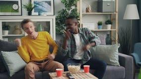 Frohe männliche Studenten passen Sportspiel, im Fernsehen auf das Lieblingsteam zu stützen, das dann klatschende Hände des Sieges stock video