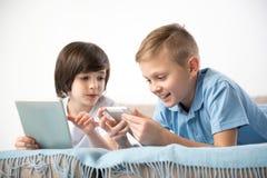 Frohe Mitschüler, die moderne Technologien einsetzen lizenzfreie stockfotografie