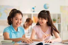 Frohe Mitschüler, die zusammen Aufgabe tun stockbilder