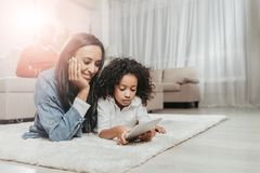 Frohe Mutter, die Aufmerksamkeit zahlt, um beim zusammen liegen zu scherzen lizenzfreie stockbilder