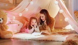 Frohe Mutter, die einen Roman mit ihrer Tochter liest stockbilder