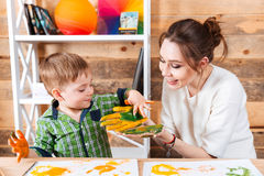 Frohe Mutter und ihre kleine Sohnmalerei auf ihren Händen Stockbilder