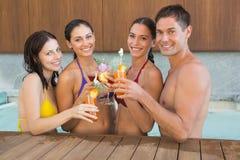 Frohe Naturen, die Getränke im Swimmingpool rösten lizenzfreies stockfoto