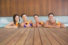 Frohe Naturen mit Getränken im Swimmingpool stockfotos
