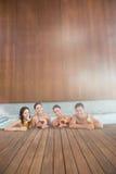 Frohe Naturen mit Getränken im Swimmingpool stockfotografie