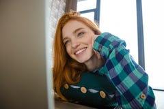 Frohe nette Frau, die auf Monitor des Laptops und des Lachens aufpasst Lizenzfreies Stockbild