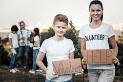 Frohe nette Frau, die ein freiwilliges Zeichen hält stockfotografie