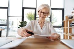 Frohe nette Frau, die einen Hefter verwendet lizenzfreie stockfotografie