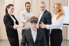 Frohe nette Leute, die um ihren Kollegen stehen Lizenzfreies Stockfoto