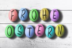 FROHE OSTERN, niemiec dla szczęśliwego Easter, pisać na barwionych Easter jajkach przeciw białemu drewnianemu stołowi fotografia stock