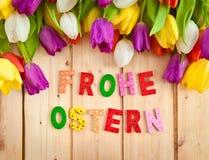 Frohe Ostern som är skriftlig i mångfärgade bokstäver Arkivfoto