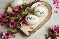 Frohe Ostern written on eggs. Happy easter written in German on white eggs with flowers frohe ostern table handwritten calligraphy decorated holiday handicraft royalty free stock photos