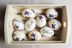 Frohe Ostern written on eggs. Happy easter written in German on white eggs with flowers frohe ostern table handwritten calligraphy decorated holiday handicraft royalty free stock images