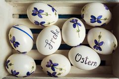 Frohe Ostern written on eggs. Happy easter written in German on white eggs with flowers frohe ostern table handwritten calligraphy decorated holiday handicraft royalty free stock image