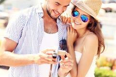 Frohe Paare, die Bilder auf der Kamera überprüfen Lizenzfreie Stockbilder