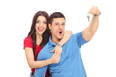 Frohe Paare, die einen Schlüssel halten und Glück gestikulieren Lizenzfreie Stockfotografie