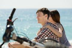 Frohe Paare, die nach dem Radfahren sich entspannen Stockbilder