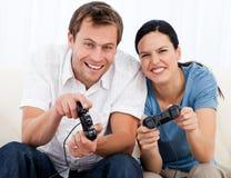 Frohe Paare, die zusammen Videospiele spielen stockfotos