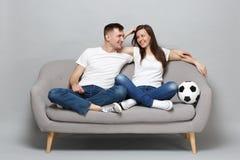 Frohe Paarfrauen-Mannfußballfane in weißem T-Shirt Beifall herauf Stützlieblingsteam mit dem Fußball, Umarmen lokalisiert lizenzfreie stockfotos