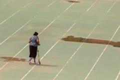 Frohe positive ältere Frau, die einen Roller beim Reiten im Park verwendet lizenzfreies stockbild