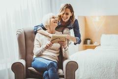 Frohe reife Frau, die ihre Enkelin betrachtet stockfotografie