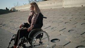 Frohe Rollstuhlfahrerfrau sitzt auf Damm Zeit festsetzen im Frühjahr und Lächeln stock video footage