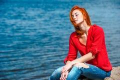 Frohe ruhige Rothaarigefrau, die bequem sitzt lizenzfreie stockfotografie