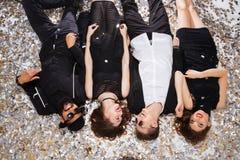 Frohe schöne Leute, die auf Hintergrund von glänzenden Konfettis sich entspannen stockbild