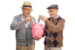 Frohe Senioren, die Geld in ein piggybank lokalisiert einsetzen Lizenzfreie Stockbilder