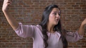 Frohe sprechende kaukasische Frau hält Smartphone in einer Hand und hat den Videoanruf und hinten steht, Ziegelstein entspannt stock video footage
