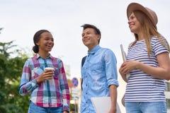 Frohe Studenten, die draußen Bruch genießen lizenzfreie stockfotos