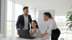 Frohe Umarmung von Mitarbeitern in den Büroräumen, erfolgreiche Geschäftsvereinbarung auf Internet auf Laptop, glückliche Teilhab