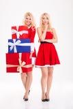 Frohe und unglückliche blonde Schwestern paart das Teilen von Geschenken Stockbilder