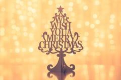 Frohe Weihnacht-beleuchtet hölzerner Weihnachtsbaum auf unscharfem Hintergrund mit goldenem bokeh Stockfotografie