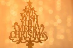 Frohe Weihnacht-beleuchtet hölzerner Weihnachtsbaum auf unscharfem Hintergrund mit goldenem bokeh Lizenzfreie Stockbilder