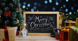 Frohe Weihnacht-Typografie auf Tafel zwischen Weihnachtsdekor stockfotos