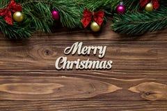 Frohe Weihnachten auf der Mitte des hölzernen Hintergrundes mit Kieferniederlassungen auf die Oberseite des Schirmes Stockfotos