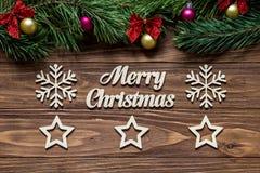 Frohe Weihnachten auf der Mitte des hölzernen Hintergrundes mit Kieferniederlassungen auf die Oberseite des Schirmes und der zwei Stockfotografie