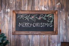 Frohe Weihnachten auf Mitteilungsanmerkung mit hölzernem Hintergrund lizenzfreies stockfoto