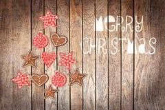 Frohe Weihnachten, Baum gemacht mit hölzernen rustikalen Verzierungen auf hölzernem Hintergrund Lizenzfreies Stockbild