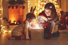 Frohe Weihnachten! Familienmutter und -kinder mit magischem Geschenk an lizenzfreie stockfotos