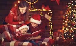 Frohe Weihnachten! Familienmuttervater und -baby lasen Buch nahe tr stockfotografie