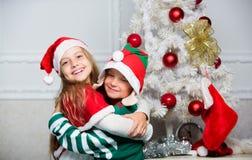 Frohe Weihnachten Familienurlaubtradition Die netten Kinder feiern Weihnachten Kinderweihnachtskostüme Sankt und Elfe lizenzfreie stockbilder