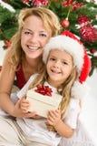 Frohe Weihnachten - Frau und Mädchen mit einem Geschenk Stockfotos