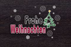 Frohe Weihnachten in german Merry Christmas with snowflakes on. Brown wood Christmas card Stock Photos