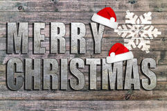 Frohe Weihnachten geschrieben auf hölzernes Brett mit Schneeflocke und Sankt Hut Lizenzfreie Stockbilder