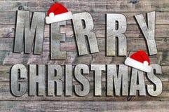 Frohe Weihnachten geschrieben auf hölzernes Brett mit Schneeflocke und Sankt Hut Lizenzfreie Stockfotos